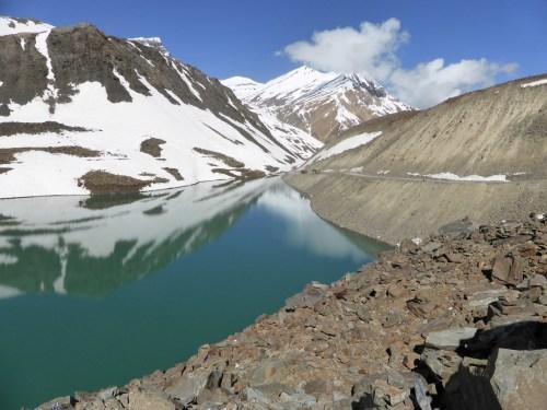 deep blue lake, snow and rocky roadside