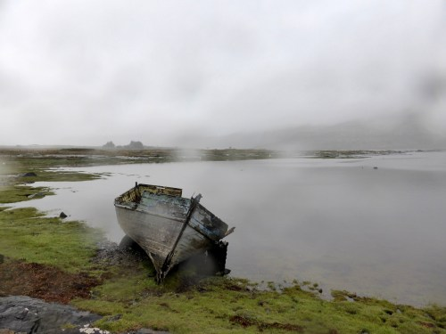 wet misty loch with boat and distant croft