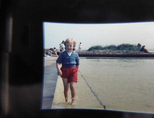 small girl in beach paddling pool