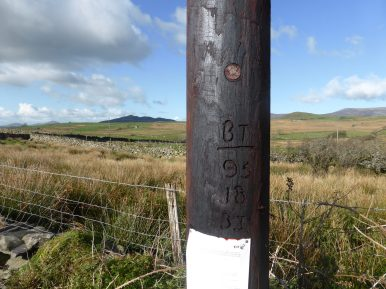 tarred BT post and view across to dark coloured hill