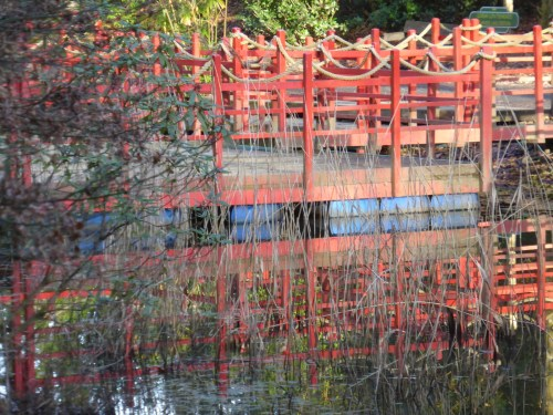 red-painted floating deck reflected on pond