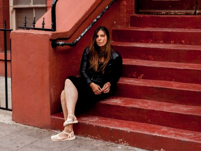 Woman dressed in black sitting on stoop.