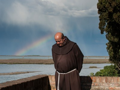A monk is adorned by a distant rainbow. Photo by Susan Wright