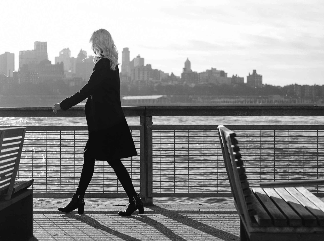 A black and white photograph of a blonde woman walking by a river