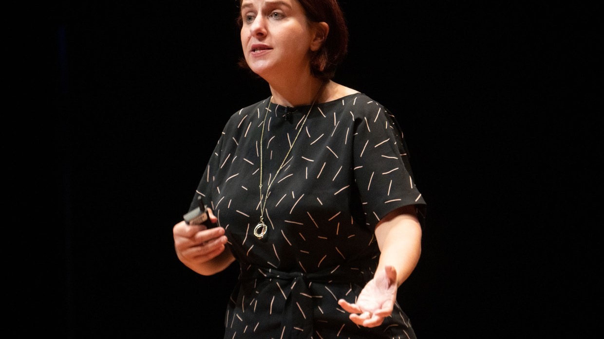 A woman in a patterned black shirt speaking onstage