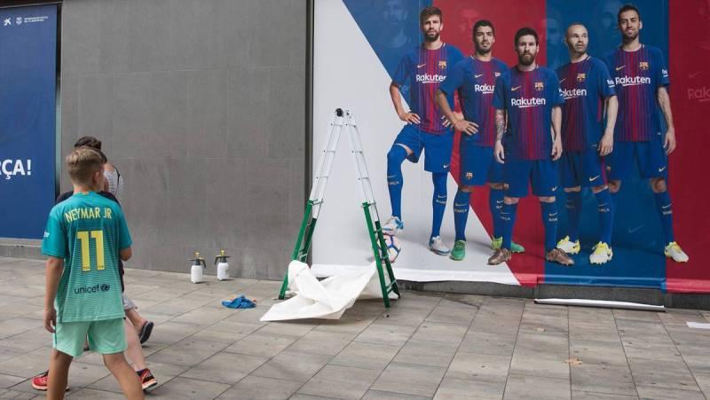 chłopak w koszulce Neymara patrzy jak usuwają go z witryn sklepowych w Barcelonie