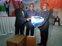 Mr Uko Umoh (l) presenting the items to the representative of a chapel