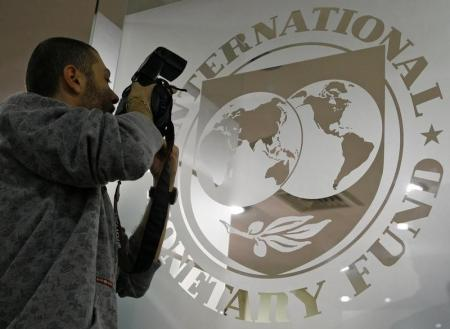 A photographer takes pictures through a glass carrying the International Monetary Fund (IMF) logo during a news conference in Bucharest, file, REUTERS/Bogdan Cristel