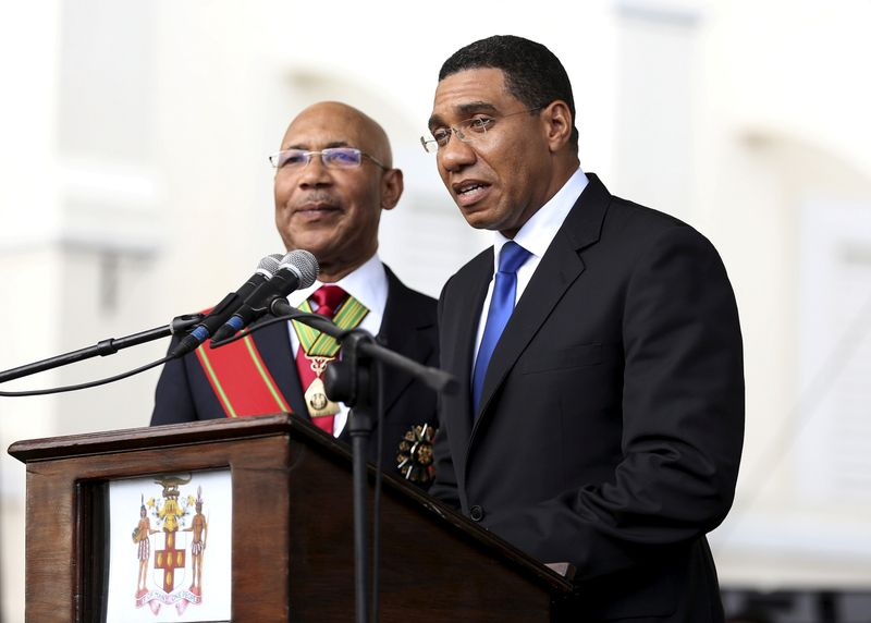 Jamaica's Prime Minister Andrew Holness (R) addresses the audience next to Jamaica's Governor-General Sir Patrick Allen during his swearing-in ceremony in Kingston,