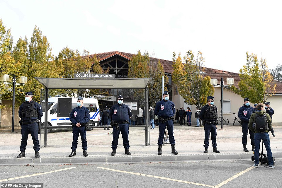 French police officers stand as adults and children gather in front of flowers displayed at the entrance of the school in Paris