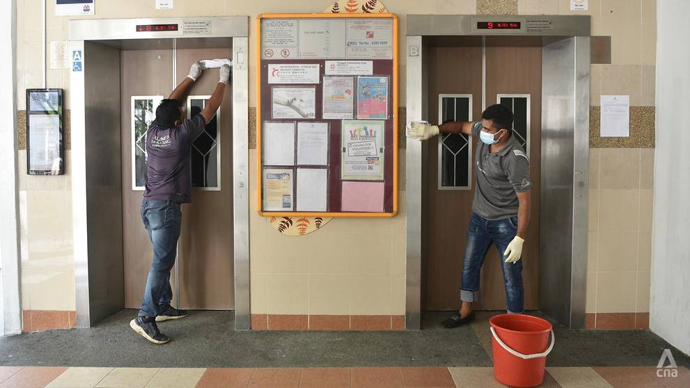 Aljunied-Hougang Town Council workers clean the lift lobby area of Block 506 Hougang Avenue 8 on May 21, 2021. (Photo- Jeremy Long)