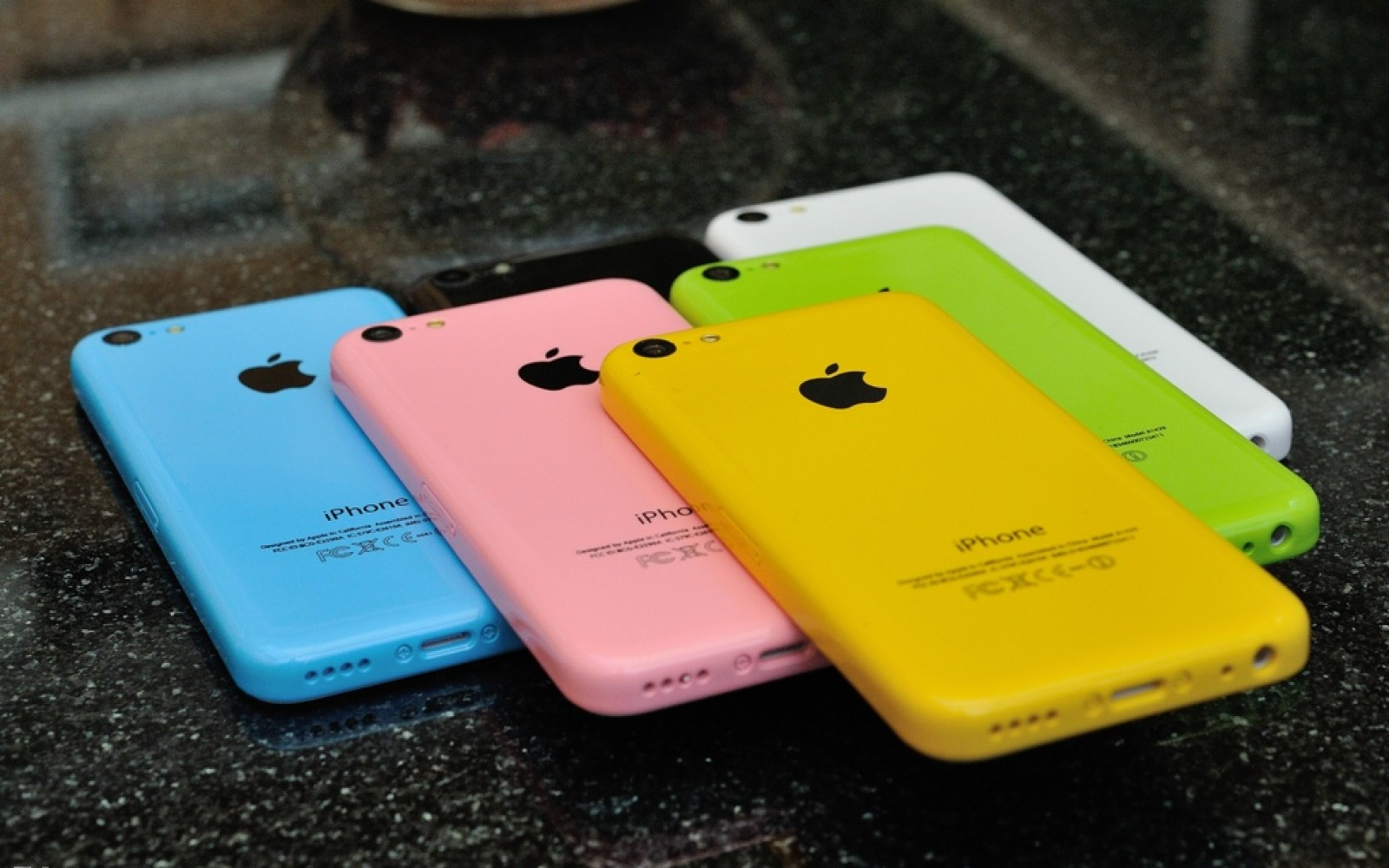 Plastic iPhone dummy units show altered color palette including pink & yellowish-orange