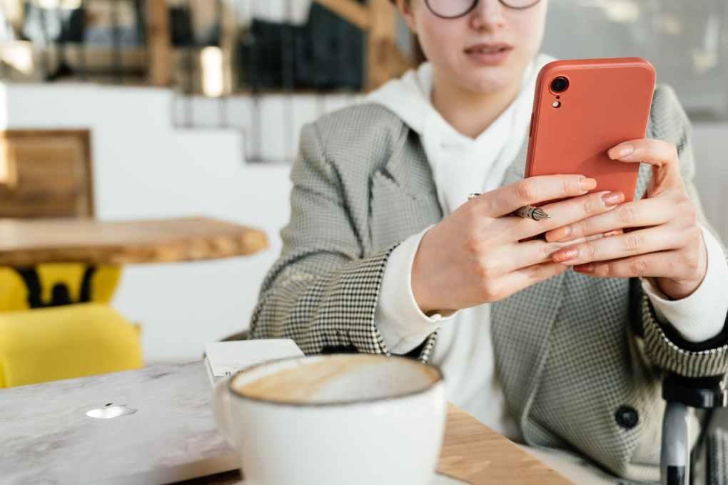 crop businesswoman using smartphone in cafe