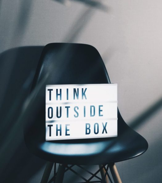 """sign with words """"think outside the box"""" on a black chair"""