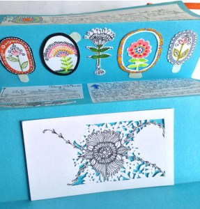 Hand written letter on white pieces of paper glued over rich blue paper, it has a row of hand painted whimsical flower stickers and a paper cut out in progress