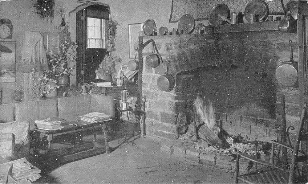 Black and white postcard showing a fireplace and living room in a rustic Normandy farmhouse.