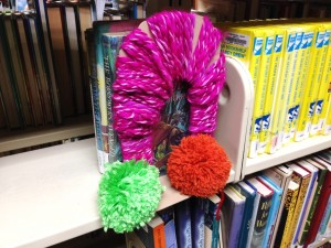 "An early example of ""yarn bombing"" on display at the Library -- a yarn-wrapped and pom-pom adorned bookend."