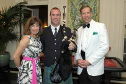 Mary and Allen Carter with the bagpiper who led the march to dinner