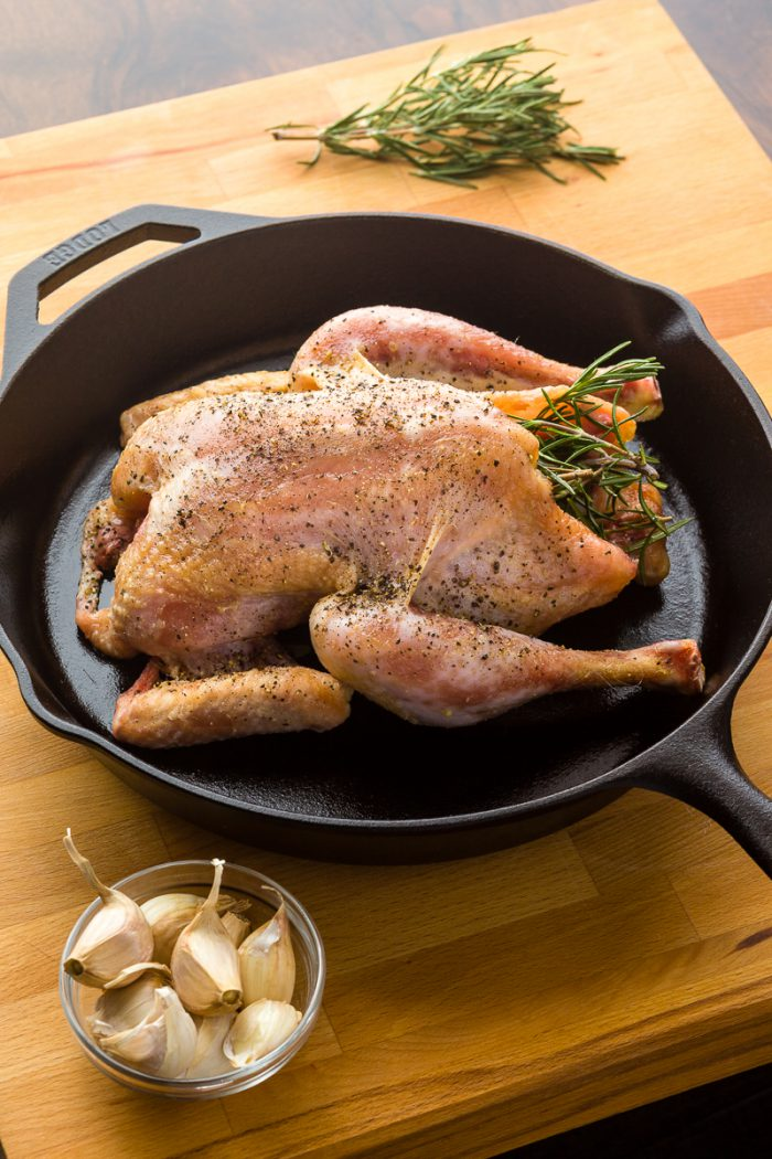 Raw chicken placed into blazing hot cast-iron skillet, to give the thighs and legs a head start.