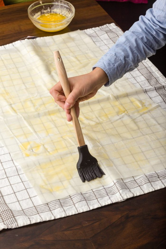 Brushing butter on the phyllo sheets will prevent them from drying and breaking while you work with them.