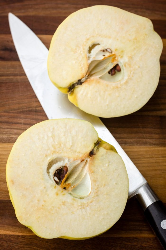 Halve the quince with big heavy knife on a stable surface. Do not core or peel for this poached quince recipe.