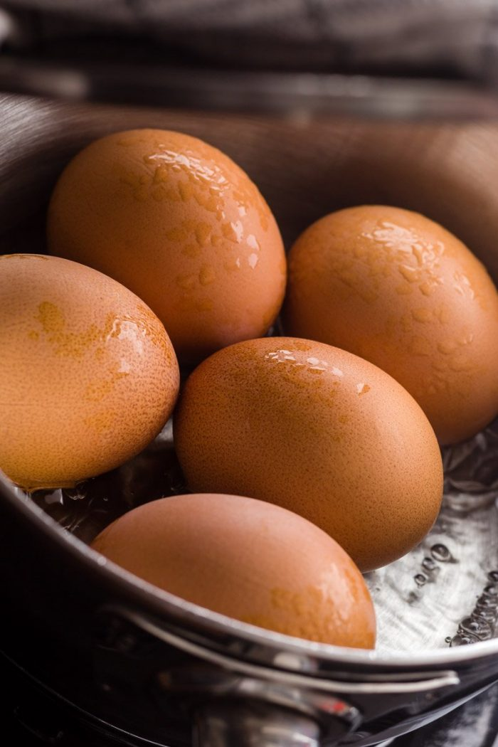 Eggs steaming with just enough boiling water in a covered pot. Steaming produces soft-boiled eggs that are a lot easier to peel.