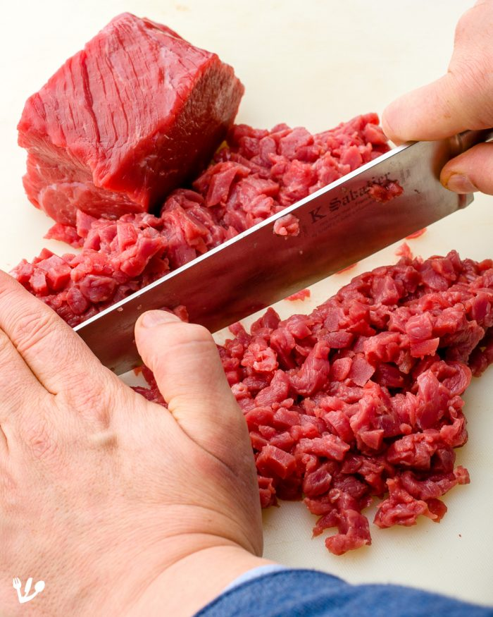 Work quickly with the well-chilled meat: First cut into thin slices, then into thin strips and then finely dice the strips.