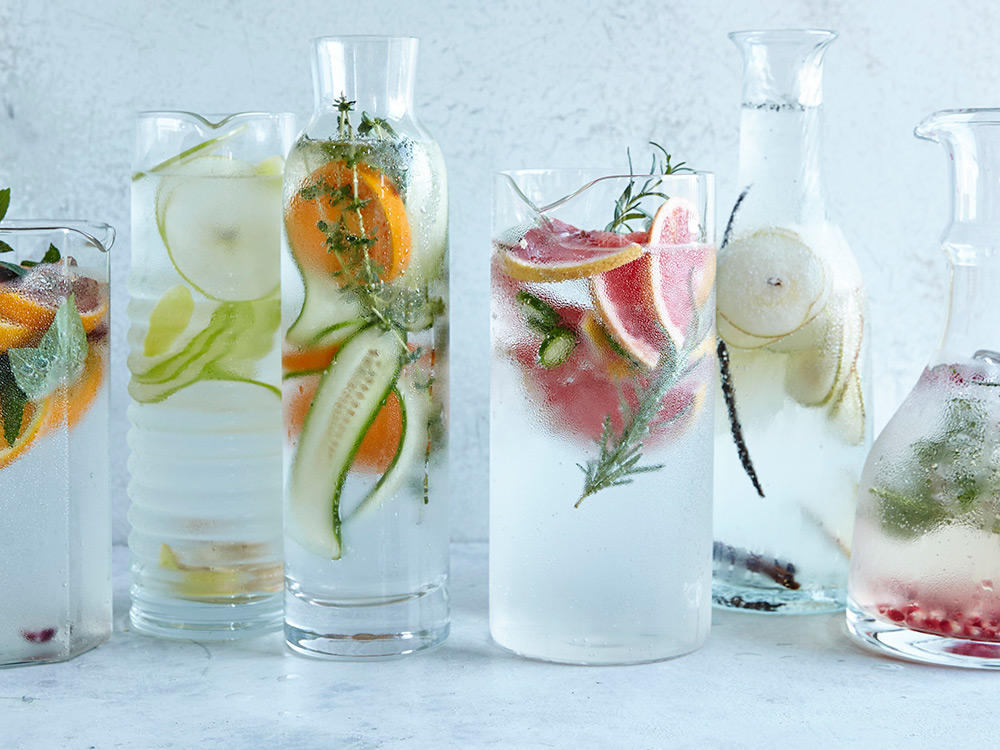 image of glass pitchers of water with different fruits and vegetables within the water
