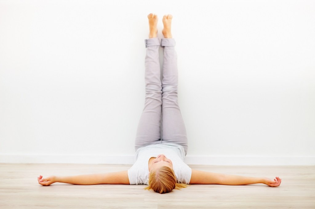 woman lying on her back with her legs up against the wall at 90% angle