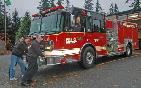 Capt. Dan Tobin has the honor of being at the wheel as firefighters Kyle Wiggins, Steve Barnes and Jason Erickson roll in Fire District 1's newest engine at Mountlake Terrace Fire Station 18 during a traditional housing ceremony.