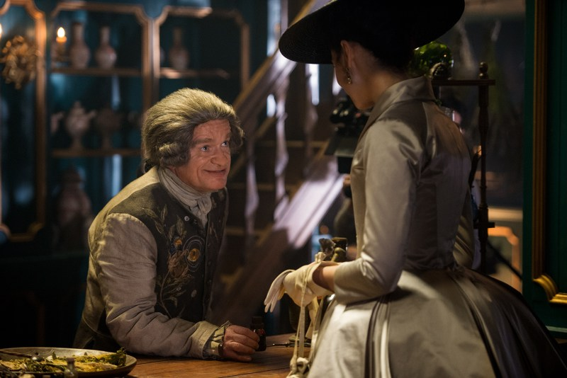 Clearly a man with such fashion sense could never be guilty. (Left, Dominique Pinon as Master Raymond speaking to Claire Fraser on the right.)