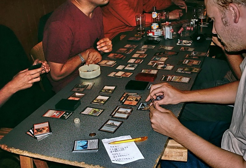 People sit at a table spread with colorfol cards. A session of Magic: The Gathering. [Courtesy Wikimedia Commons]