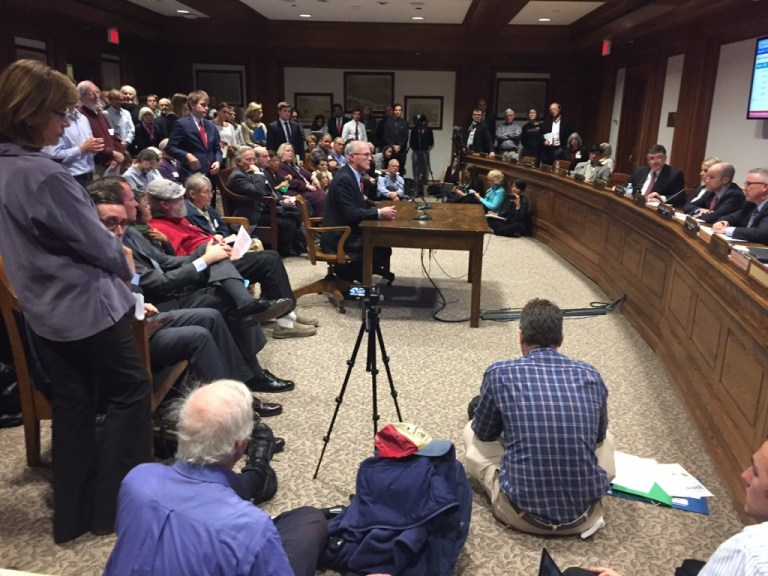 Sen. Barrett testifies on carbon pricing at a packed committee hearing.