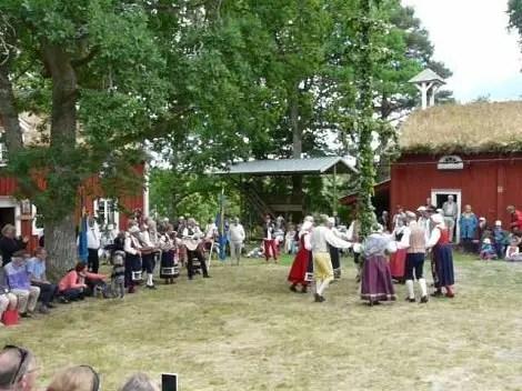 La gente bailando alrededor de Midsommarstånget en esta gran fiesta.