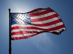 jnn1776-usa-american-flag-sun-glare-background-blue-sky-wind-us
