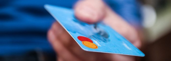 money-payment-credit-card-hand-holding-blurry-background-crop