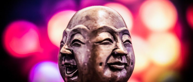 stone buddha face smiling expression bokeh blurry background Thinking Theatre