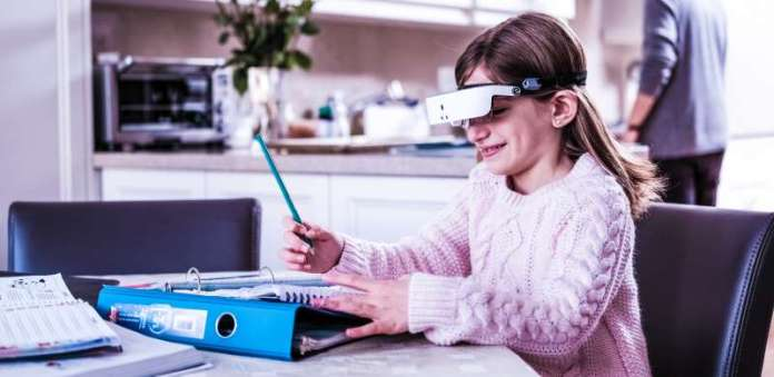 eSight Wearable Legally Blind Low Vision Young Child Girl Doing Homework Home Studying School Learning Reading Writing Table