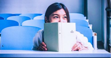 Asian girl reading book in class smiling happy studying sitting indoors science books list must read