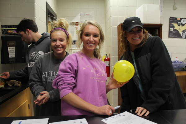 Students in Mrs. McAllister's Forensics class pridefully hold up their balloon after the DNA Fingerprinting lab.
