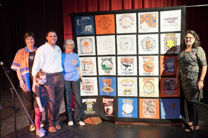 QUILTY PLEASURE --Quilter Pat Coleman (far left) of Remembering Mayberry chapter in Chillicothe, Ohio, made this quilt of T-shirts from each of the 25 Mayberry Days festivals to date. The back of the quilt was signed by this year's festival guest stars. The quilt was auctioned as a Mayberry Days fundraiser during this year's festival.  Auctioneer Dustin Rogers (left) encouraged lively bidding as his mom, Deidre Rogers (far right), also of Rogers Realty & Auction, looked on.  In the end, the quilt sold for a whopping $6,200 to Betty Blackmon (in blue T-shirt), aka to Dustin as Memaw. It was a spectacular result...one truly for the generations.  (An unidentified waist-high member of yet another generation of the Rogers family is also pictured.) Photo by Hobart Jones.