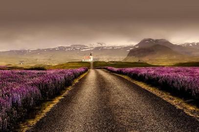 Eine Straße zieht sich durch die atemberaubende Landschaft von Island.