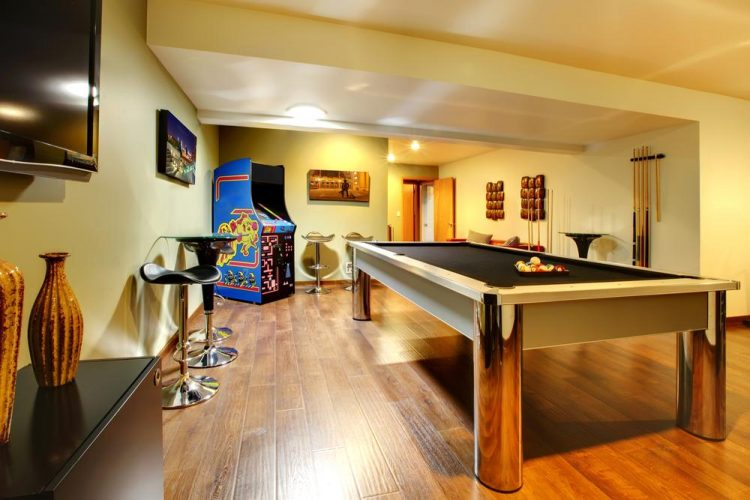 Fun play room home interior. Basement room without windows with pool table, TV, games.