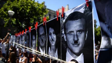 Владелец французского билборда получил штраф в размере 10000 евро за изображение президента Макрона в образе Гитлера на плакате протеста против Covid