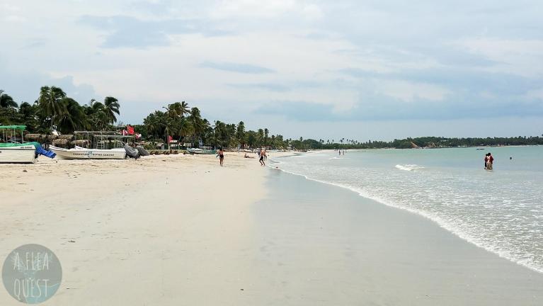 La plage des touristes, avec en décor buccolique un couple amoureux qui joue et des baigneurs