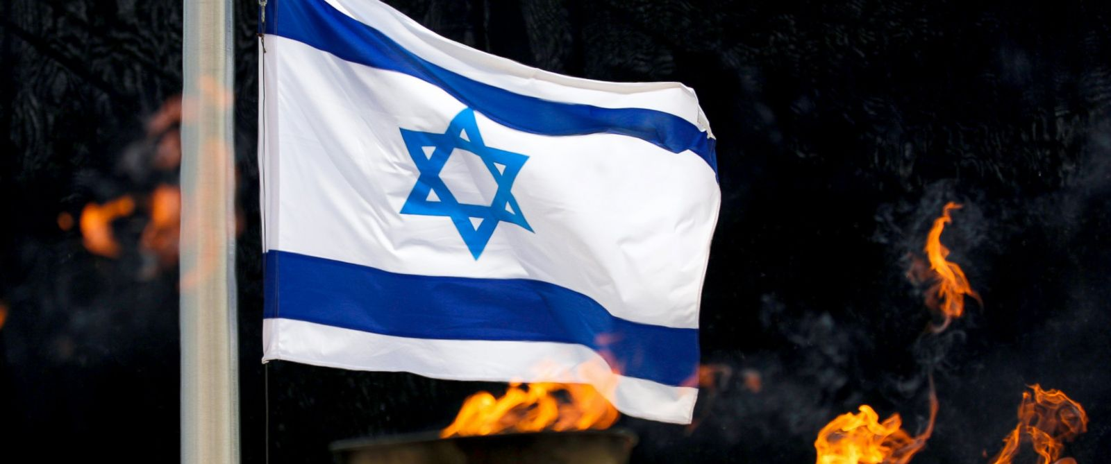 PHOTO: An Israeli flag behind torches is seen during the annual Holocaust Remembrance Day at the Yad Vashem Holocaust memorial in Jerusalem, Israel, April 24, 2017.