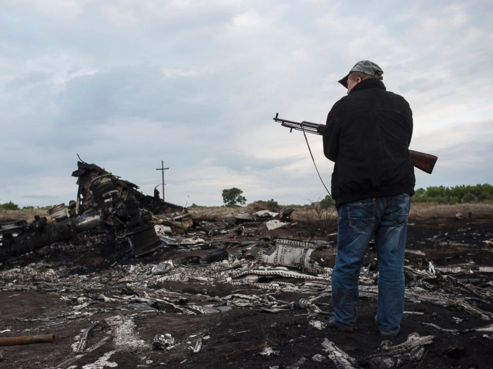PHOTO: A pro-Russia fighter stands on guard the crash site of a Malaysia Airlines jet near the village of Hrabove, eastern Ukraine, Saturday, July 19, 2014.