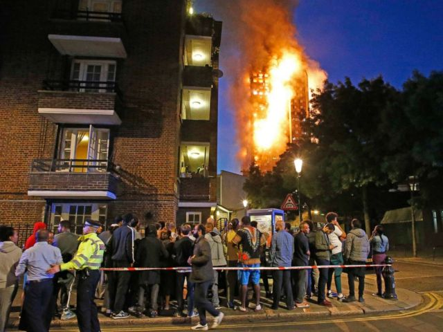 PHOTO: People watch the Grenfell Tower fire as it burns in the early hours of June 14, 2017 in London.