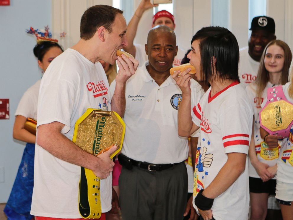 PHOTO: Brooklyn Borough President Eric Adams watches Joey Chestnut, left, and Matt Stonie, right, during a news conference to promote the upcoming Nathans Famous Fourth of July Hot-Dog Eating Contest, July 3, 2015, at Brooklyn Borough Hall in New York.