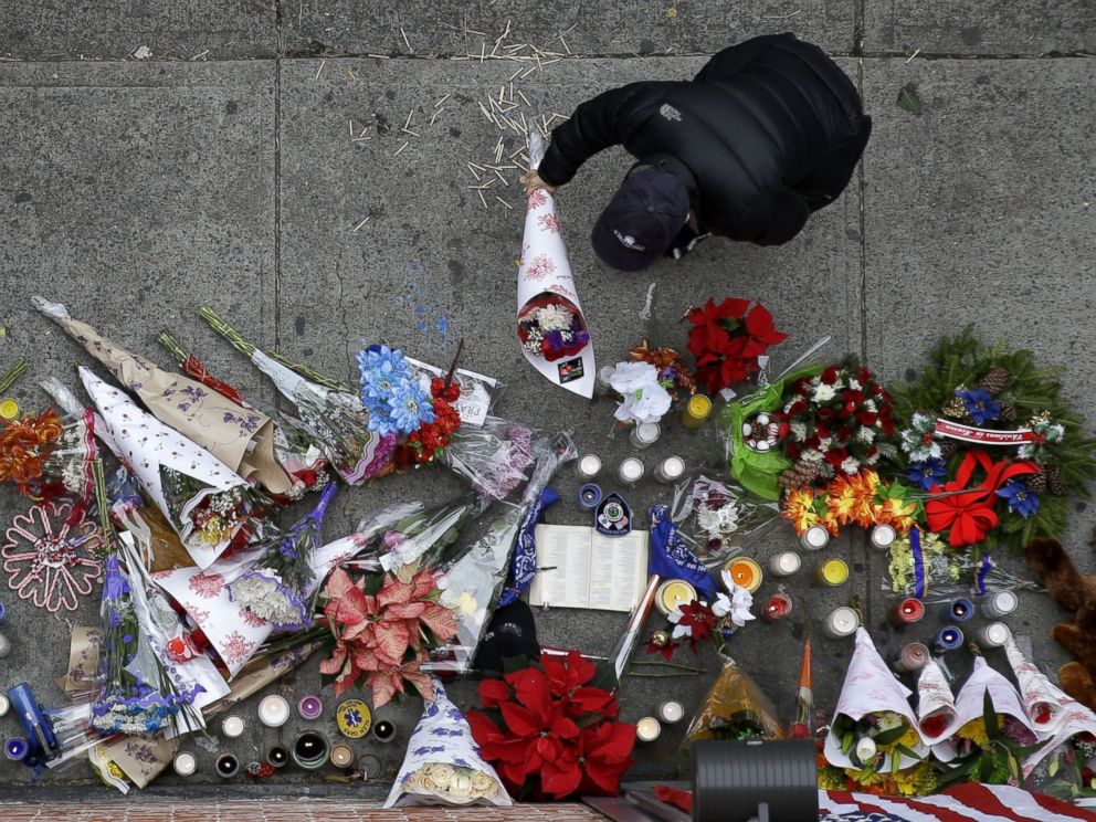 PHOTO: A man leaves flowers at an impromptu memorial near the site where two police officers were killed the day before in the Brooklyn borough of New York, Dec. 21, 2014.